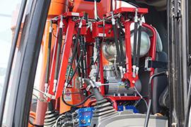 バックホーの操縦席に収められたロボット。伸縮する人工筋肉とエアーコンプレッサーが見えます。