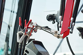 ロボットから伸びるアームが、各種操縦レバーに固定されています。