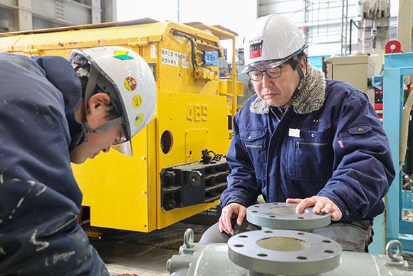 エンジニアリング事業部 機械メンテナンス課 業務 事務部課長の三瓶武啓(写真右)。全体の管理が主な業務で、現場での指導、相談も大切な役務