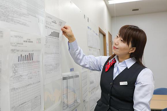事務の生澤恵子さん。朝の発注業務に始まり、社内メール便の伝票発行、作業書の入力作業、見積書の作成など、業務内容は多岐にわたる。写真は会議室に掲出する実施計画書・実施事項管理表の入れ替え作業