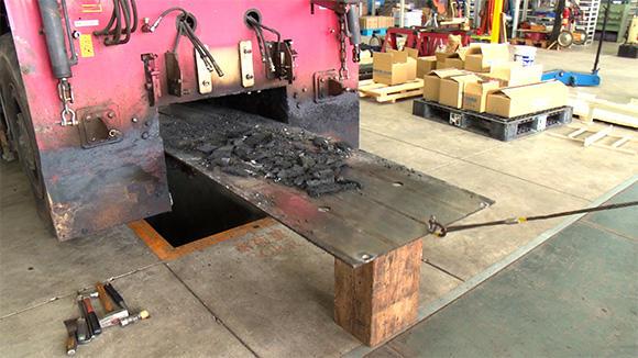 今回交換する中で最も大物の部材、コンベア底板。バールでスファルトの固着を剥がし、ワイヤーで引っ張り出す