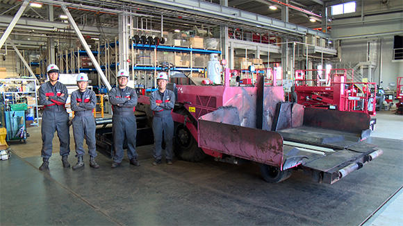 オーバーホールが完了した車体と、整備を担当したアクティオ九州道路機械工場のメンバー