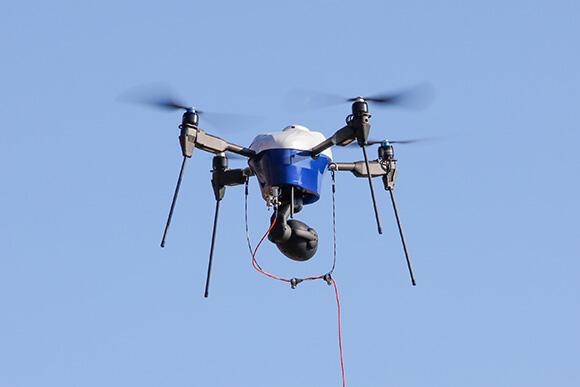 有線ドローン「エアロボオンエアー」(エアロセンス)を使用。電源から直接電力供給のため、長時間の飛行が可能だ。また、4Kの映像を非圧縮・リアルタイムで伝送できるため、今回のような重機の位置確認用にも向いている