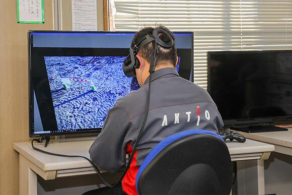 「監視室」では、無人バックホーの前方映像も表示される。ヘッドマウントディスプレイ(HMD)による映像確認も可能である