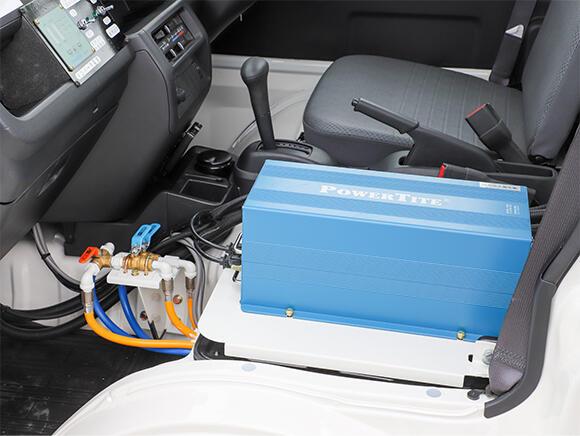 助手席があった場所に、自動車が発電した電力(直流)を交流に変換するDC-ACインバーターが設置されている。その左に見えるのは前方加圧散水用の三方弁。インストルメントパネル(インパネ)にはインバーターやポンプのスイッチなどを配置